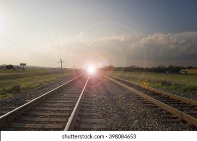 Light on the Tracks. There is light off in the distance on these RR tracks with cloudy weather and lens flare.
