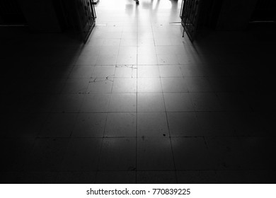 The light from the outside shine into the dark room. The lines on the floor lead outwards.