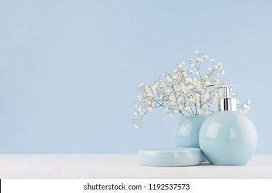 Light pastel blue ceramic acessories for bath  - bowl, vase, soap dispenser, flowers on white wood table. Decor for bathroom interior.