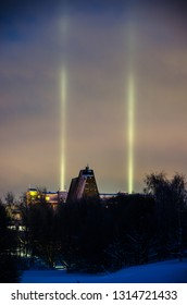 Light pillars in frosty evening behing old pulp mill silo in Oulu, Finland.
