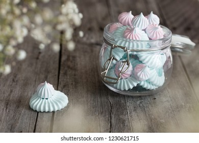 Light Pink and blue meringues in glass jar on dark background
