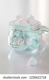 Light Pink and blue meringues in glass jar on pink background, vertical composition