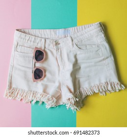 light pink denim shorts with fringe and sunglasses on colorful paper background in style pop art