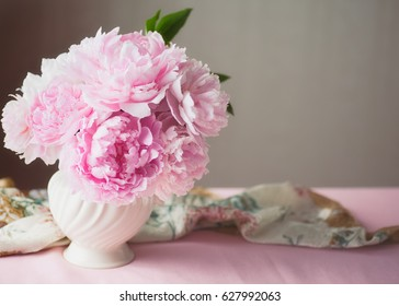 Light pink double Peonies in white ceramic vase with silk scarf on table and copy space.