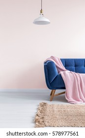 Light pink living room with blue sofa, rug and lamp