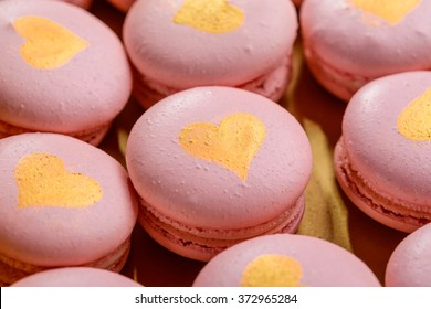 Light pink macaroon decorated with a heart of gold close-up. A gift on Valentine's Day.