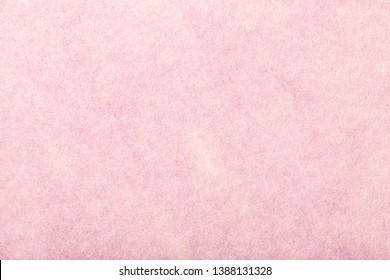 Light pink matte background of suede fabric, closeup. Velvet texture of seamless rose woolen felt.