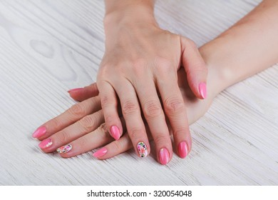 Light pink nail art with printed flowers on white background