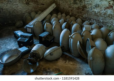 Light pole heads/old prison cell used as a deposit for obsolete objects such as light pole heads and television sets.