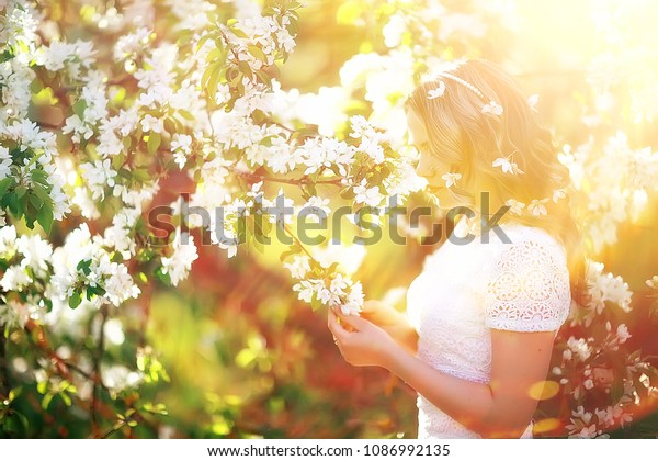 light portrait of an apple tree, girl portrait of a high key, spring mood freshness and purity blonde with long hair in a blooming park in the spring