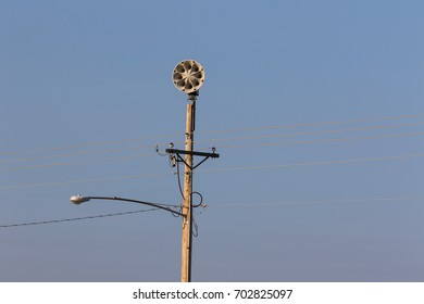 a light, power lines and civil defense on a pole