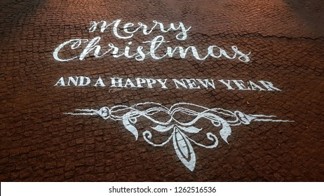 Light projection inscription Merry Christmas and Happy New Year with ornate monogram on stone pavement near Christmas Garden Berlin in Germany. Christmas lights. Vintage style lettering. Illumination