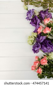 Light purple eustoma flowers  and pink shrub rose on white wooden background with empty space for text. Top view with copy space.