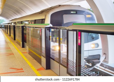 Light rail transit train arrives at a station in Singapore. Metro train motion blur