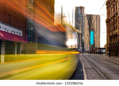 Light rail yellow tram in the city center of Manchester, UK in the evening. Motion blurred tram with modern buildings