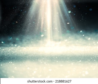 Light rays from top on the black blurren plane with bekeh lights
