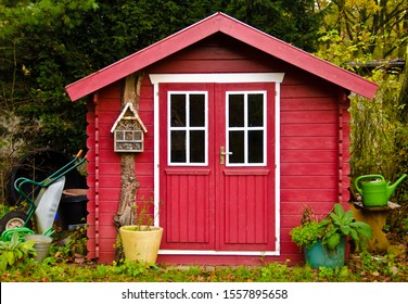 A light red small shet, gardenhouse, with some garden tools around it