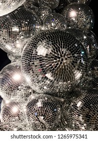 Light reflects and bounces off shiny disco balls of various sizes set on a dark black background.