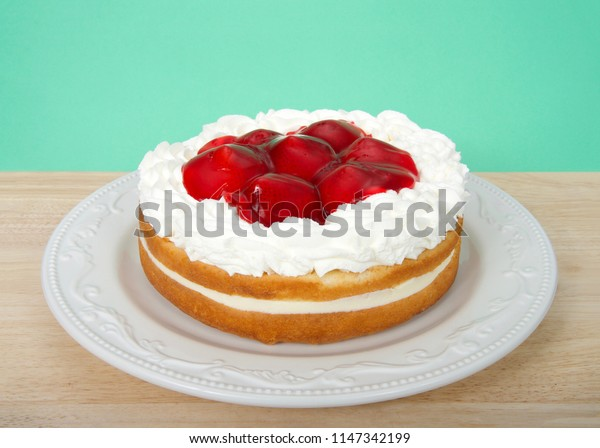 Light refreshing vanilla cake with cream filling, topped with whipped cream and glazed whole strawberries on a light wood table with light green background. Fresh summer fruit.