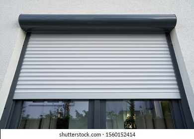 Light roller shutter curtains mounted on a dark window