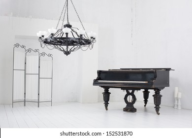 A light room with a piano, a folding screen and a chandelier