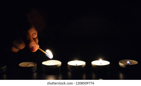 light up a row of candles in the dark with a match - light up candle in a cold evening with focus on the candle and low lightning