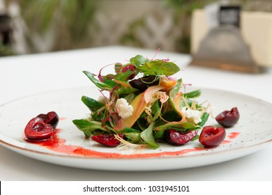 Light salad with soft cheese and cherry dressing on restraurant table