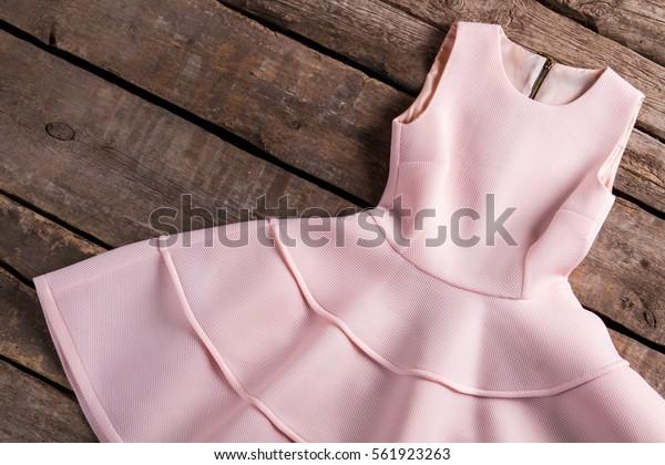 Light salmon dress with folds. Dress on old wooden background. Garment at vintage fashion house. Festive sleeveless dress.