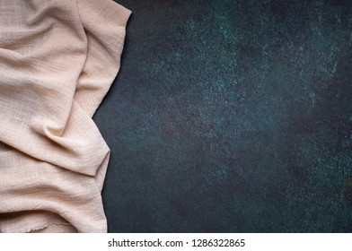 Light scarletish gray tablecloth from left side of dark background