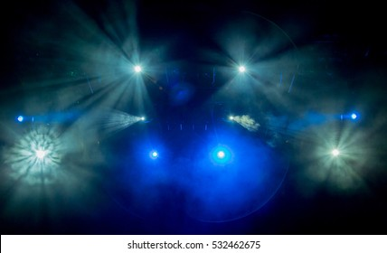 The light of searchlights in smoke on stage of the theatre.