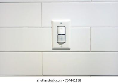 Light sensor on white tiled wall