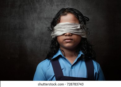 Light and shade portrait of a blindfolded school girl in a dark background