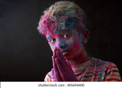 Light and shade portrait of boy with face smeared with colored powder in a dark background. Concept for Indian festival Holi