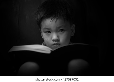 Light and shadow of little boy sitting at the desk and reading a book