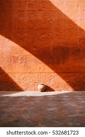 Light and shadow on a bright orange painted wall