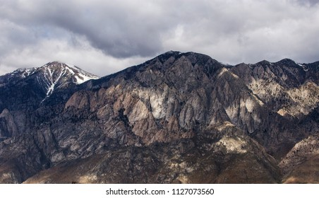 Light and shadow play on the face of towering colorful rock mountains near Mammoth Mountain in the Eastern Sierra with some snow remaining on the crest and moody gray storm clouds over them.