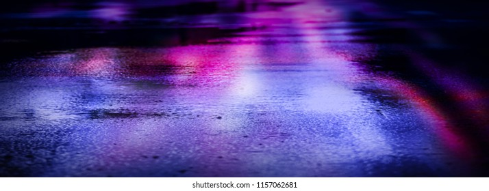 Light and shadows of the night city. Wet asphalt with neon. Soft image of the focus of the street after the rain with reflections on the wet asphalt. Blurred background.