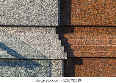 Light and shadows on the surface of granite wall of building. Close up view of part of a building facade. Natural stone surface.