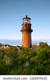 Light shines from the brick tower of Aquinnah lighthouse as the sun sets on a summer day on the island of Martha's Vineyard.