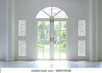The light shines on the white door. When look outside, there is a green tree. Look so refresh.