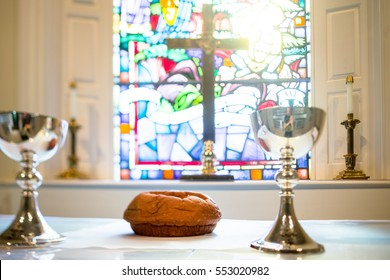 Light shines through a beautiful stained glass window in Methodist church around gleaming golden cross onto two metallic chalices and loaf of communion bread.