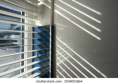 Light shines through blinds on a sunny day.