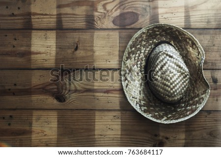 55fa9099 Light shining through onto a straw hat hanging on a wooden wall,Concept  travel and