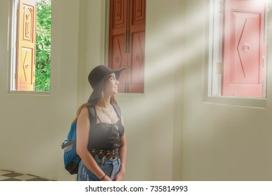 Light shining through the window, smiling Asian girl In churches, temples in Thailand