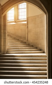 Light shining through windows onto stone stairs stairway staircase under a gothic archway. Ivy league college university architecture concept future ambition opportunity potential. success concept