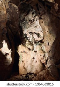 Light shinning through the giant crevices onto stalactites and stalagmites in an ancient underground cave.