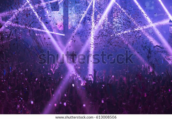 Light Show And Silhouette hands of audience crowd people use smart phones enjoying the club party with concert.  Blurry night club DJ party people enjoy of music dancing sound.Abstract Background.