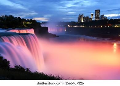Light showcase lighting cascades of water Niagara Falls. Illuminated night view of Niagara Falls. USA.