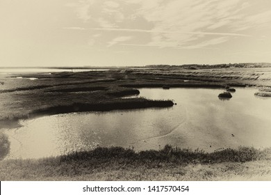 Light and sky reflections on water in Orford Marshes, Ore Estuary, Suffolk, UK. Grainy antique vintage sepia effect.
