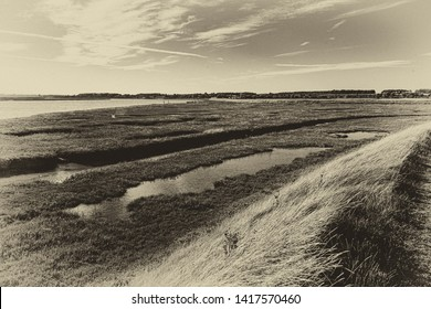 Light and sky reflections on water with dramatic clouds over Orford Marshes, Ore Estuary, Suffolk, UK. Grainy antique vintage sepia effect.